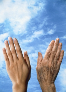 Hand of an old and of a young woman in front of cloudy sky